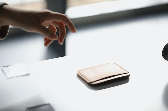 Reaching for a Tan Makr Round Luxe wallet in Seoul.